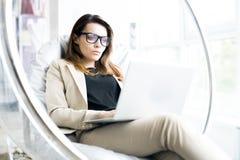 Donna di affari moderna Resting in ufficio immagine stock