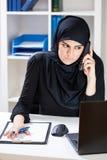 Donna di affari musulmana che parla sul telefono Immagine Stock