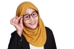 Donna di affari musulmana sorridente Adjusting Eyeglasses immagine stock
