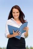 Donna di affari nei dispositivi di piegatura sorridenti della stretta della natura piena di sole Fotografia Stock Libera da Diritti