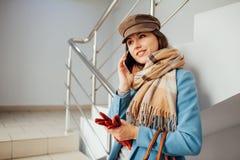 Donna di affari nei supporti del cappotto sulle scale nel centro commerciale con lo smartphone Acquisto Modo fotografia stock libera da diritti