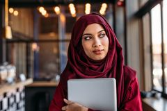 Donna di affari nel hijab con il computer portatile a distogliere lo sguardo del caffè fotografia stock libera da diritti