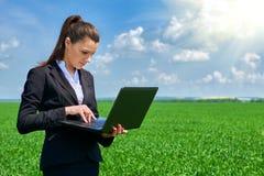 Donna di affari nel lavoro all'aperto del campo di erba verde sul computer portatile Ragazza vestita in vestito nero Bello paesag Immagini Stock Libere da Diritti