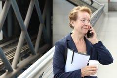 Donna di affari nell'aeroporto o nella stazione della metropolitana del sottopassaggio del treno che fa una telefonata con lo sma Immagine Stock Libera da Diritti