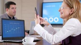 Donna di affari nell'auditorium che esamina telefono archivi video