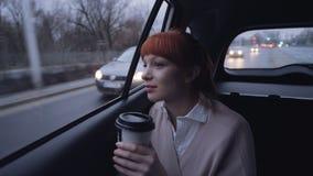 Donna di affari nell'automobile che beve dal recipiente del caffè