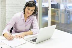 Donna di affari nell'ufficio sul telefono con la cuffia avricolare, Skype Fotografie Stock