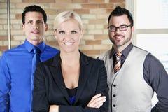 Donna di affari nella parte anteriore con due uomini di affari nel sorridere posteriore Fotografia Stock