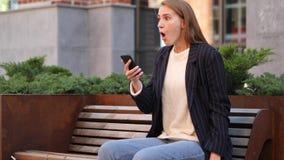 Donna di affari nella scossa che reagisce ai risultati su Smartphone immagine stock