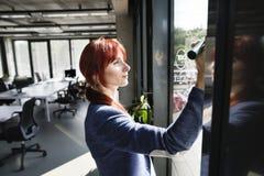 Donna di affari nella sua nota di scrittura dell'ufficio sulla finestra Fotografia Stock Libera da Diritti