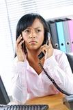 Donna di affari nera che per mezzo di due telefoni allo scrittorio Fotografie Stock Libere da Diritti