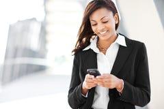 Donna di affari nera che texting Fotografie Stock Libere da Diritti