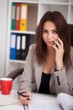 Donna di affari nera sorridente sul telefono allo scrittorio fotografia stock libera da diritti