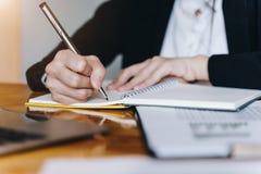 Donna di affari o segretario che giudica penna d'argento pronta a fare nota in strato aperto del taccuino Finanze di affari e con immagine stock