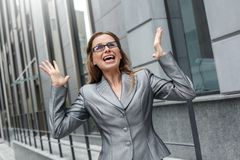 Donna di affari in occhiali che stanno sulle mani della via della città su sorpresa con l'idea immagini stock