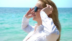 Donna di affari in occhiali da sole sulla spiaggia Si rallegra nel mare e nel sole Ha sbottonato la sua camicia e inspira immagini stock libere da diritti