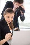 Donna di affari osservando computer portatile con la lente d'ingrandimento Fotografia Stock