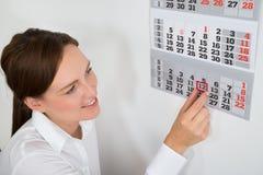 Donna di affari Placing Red Mark On Calendar Date Fotografia Stock