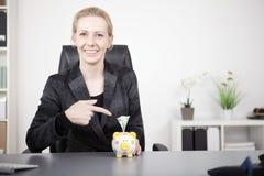 Donna di affari Pointing al porcellino salvadanaio con contanti Fotografie Stock