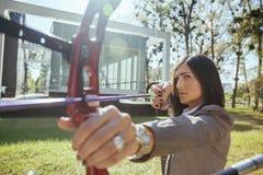 Donna di affari Pointing The Target con l'arco e la freccia immagini stock
