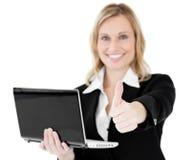 Donna di affari positiva che tiene un pollice del computer portatile in su Fotografie Stock