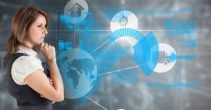 Donna di affari premurosa che guarda schermo digitalmente futuristico con le icone immagine stock