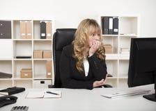 Donna di affari premurosa che legge il suo monitor Immagini Stock