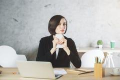 Donna di affari premurosa che per mezzo dello smartphone nel luogo di lavoro Fotografia Stock