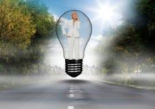 Donna di affari premurosa che sta nella lampadina sopra la strada contro il cielo Fotografia Stock Libera da Diritti