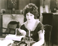 Donna di affari premurosa con la macchina da scrivere allo scrittorio in ufficio Immagine Stock