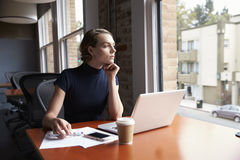 Donna di affari premurosa Working On Laptop dalla finestra fotografia stock