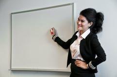 Donna di affari presente con il bordo di tiraggio su fondo bianco immagine stock