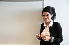 Donna di affari presente con il bordo di tiraggio su fondo bianco fotografia stock