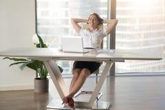 Donna di affari Relaxing With Hands dietro la testa immagini stock libere da diritti