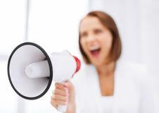 Donna di affari rigorosa che grida in megafono Immagine Stock