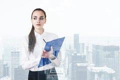 Donna di affari rigorosa con la lavagna per appunti, città Fotografie Stock Libere da Diritti