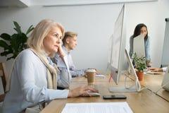Donna di affari senior messa a fuoco che lavora al desktop che si siede a offic fotografie stock