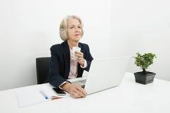 Donna di affari senior premurosa che mangia caffè allo scrittorio in ufficio Immagine Stock