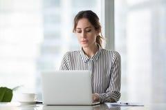 Donna di affari seria che lavora online facendo uso del computer portatile all'ufficio immagine stock libera da diritti