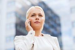 Donna di affari seria con lo smartphone all'aperto Fotografie Stock