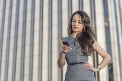 Donna di affari seria con lo smartphone sopra l'edificio per uffici Fotografie Stock