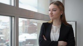 Donna di affari seria in vestito nero che guarda alla finestra in ufficio moderno stock footage