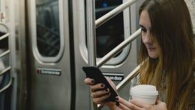 Donna di affari sicura attraente felice in metropolitana facendo uso del app online dell'ufficio mobile sullo smartphone e sul so archivi video