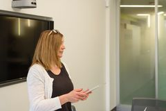 Donna di affari sicura che presenta nella sala con la compressa ed il video immagine stock