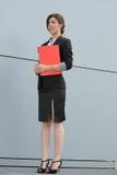 Donna di affari sicura che tiene un dispositivo di piegatura rosso Fotografia Stock Libera da Diritti