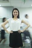 Donna di affari sicura con i colleghi precipitanti dietro lei Fotografia Stock Libera da Diritti