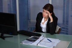 Donna di affari sollecitata che lavora nell'ufficio Fotografie Stock Libere da Diritti