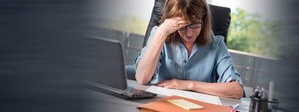 Donna di affari sollecitata che si siede nell'ufficio Fotografie Stock Libere da Diritti