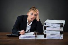 Donna di affari sollecitata Looking At Folders mentre lavorando allo scrittorio immagini stock