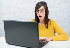 Donna di affari sorpresa che per mezzo del suo computer portatile Fotografia Stock Libera da Diritti